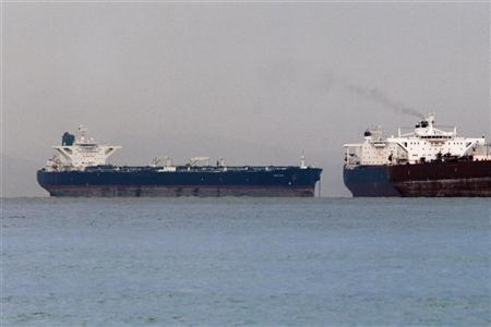 "Vessels sail past Malta-flagged Iranian crude oil   supertanker ""Delvar"" (L) anchoring off Singapore March 1, 2012. REUTERS/Tim Chong"