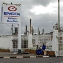 Workers sit outside Durban's Engen Oil Refinery after fire broke out