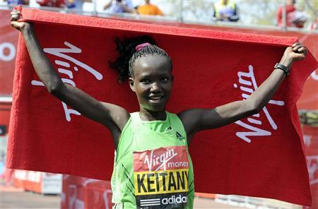 Mary Keitany of Kenya poses for photographers after   winning the women's section of the London Marathon April 17, 2011. REUTERS/Paul Hackett