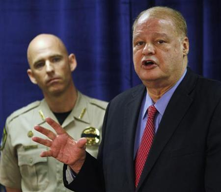 """Pinal   County Sheriff Paul Babeu (L) listens as Arizona Attorney General Tom Horne speaks about weapons and drugs seized from the   Mexican Sinaloa cartel during """"Operation Pipeline Express"""" at a news conference in Phoenix, Arizona October 31,   2011. REUTERS/Joshua Lott"""