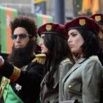 Actor Sacha Baron Cohen, playing Admiral General Aladeen, points a gun as he poses with models at the world premiere of the Dictator at the Royal Festival Hall in London May 10, 2012. REUTERS/Dylan Martinez (BRITAIN - Tags: ENTERTAINMENT SOCIETY)