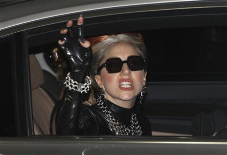 U.S. singer Lady Gaga waves upon her arrival for her concert tour, at Don Muang Airport in Bangkok May 23, 2012. REUTERS/Sukree Sukplang