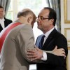 """France's newly-elected President Francois Hollande is awarded """"Grand Maitre"""" in the Order of the Legion of Honour, from chancellor of France's National Order of the Legion of Honour, General Jean-Louis Georgelin, as he is officially named President at the handover ceremony at the Elysee Palace in Paris May 15, 2012. REUTERS/Fred Dufour/Pool"""