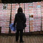 A parent looks at posters with personal information displayed during a Valentine's Day event at the People's Park in Shanghai, February 14, 2012. REUTERS/Aly Song