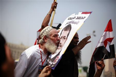 """A supporter of the Muslim Brotherhood's presidential candidate Mohamed Morsy kisses a picture of him during a celebration at Tahrir square in Cairo June 18, 2012. The Muslim Brotherhood's Mohamed Morsy said on Monday after his group declared him winner in a presidential race that he would be a president for all Egyptians and said he would not """"seek revenge or settle scores."""" REUTERS/Suhaib Salem"""