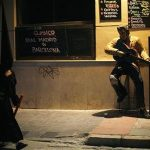 """A penitent walks past a statue of Elvis Presley placed outside a bar as he leaves the procession of """"Salesianos"""" brotherhood during Holy Week in the An dalusian city of Malaga, southern Spain, April 20, 2011. REUTERS/Jon Nazca"""