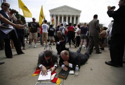 Religious leaders lay on the ground and pray over a bible and a copy of the verdict on President Barack Obama's signature healthcare overhaul law outside the Supreme Court in Washington June 28, 2012. REUTERS/Jason Reed