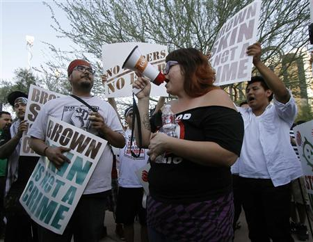 People hold signs as they gather during a protest against Senate Bill 1070 (SB-1070), in front of the Immigration and Customs Enforcement offices in Phoenix, Arizona, June 25, 2012. REUTERS/Darryl Webb