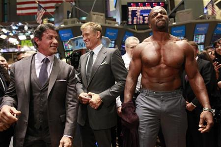 """Actor Terry Crews (R) poses shirtless next to his fellow """"The Expendables"""" cast members Sylvester Stallone (L) and Dolph Lundgren (C) for photographers on the floor of the New York Stock Exchange August 19, 2010. Cast members from the film rang the opening bell at the New York Stock Exchange on Thursday. REUTERS/Brendan McDermid"""