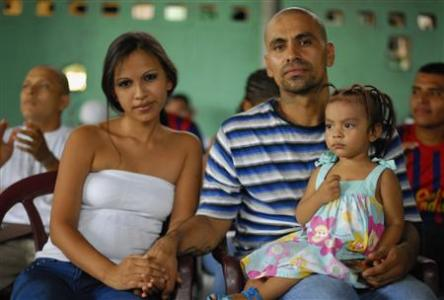 "Victor Garcia (R), alias ""The Duck"" from the Calle 18 gang, sits with his wife and daughter during a religious service at a prison in Quezaltepeque, on the outskirts of San Salvador June 16, 2012. The relentless tit-for-tat murders between El Salvador's two largest street gangs - ""Calle 18"" and ""Mara Salvatrucha"" - made the country the most murderous in the world last year after neighboring Honduras, also ravaged by gang violence. That was until Garcia, from the Calle 18 (""18th Street"") gang, along with elders from the Mara Salvatruchadeclared an unprecedented truce that authorities say has cut the homicide rate in half in just four months. Picture taken June 16, 2012. REUTERS/Ulises Rodriguez"