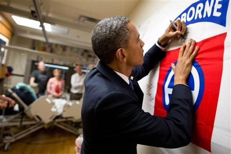 U.S. President Barack Obama autographs a banner while visiting a wounded service member at Walter Reed National Military Medical Center in Bethesda, Maryland, in this June 28, 2012 photograph obtained on July 19, 2012. REUTERS/Pete Souza/Handout