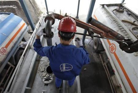 An employee fills the tank of a petrol delivery vehicle at a Sinopec refinery in Wuhan, Hubei province, April 25, 2012. REUTERS/Stringer