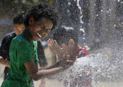 Aziz Taylor, 11 years old, of Washington DC, plays in a water fountain to beat the heat gripping the nation's capital while in the Capital Heights neighborhood of Washington, July 2, 2012. REUTERS/Larry Downing