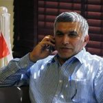 Bahrain human rights activist Nabeel Rajab talks on his mobile phone as a miniature Bahrain Pearl Square monument is seen behind him, upon arriving home in Budaiya, west of Manama, after being detained for over two weeks, May 28, 2012. REUTERS/Hamad I Mohammed