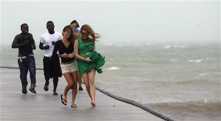 A group of people run back to shore along a pier in high wind and rough surf as Tropical Storm Isaac moves over Key West August 26, 2012. REUTERS/Andrew Innerarity