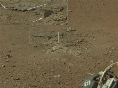 This color image from NASA's Curiosity rover, taken August 8, 2012 and released by NASA August 12, 2012, shows an area excavated by the blast of the Mars Science Laboratory's descent stage rocket engines. This is part of a larger, high-resolution color mosaic made from images obtained by Curiosity's Mast Camera. With the loose debris blasted away by the rockets, details of the underlying materials are clearly seen. Of particular note is a well-defined, topmost layer that contains fragments of rock embedded in a matrix of finer material. Shown in the inset in the figure are pebbles up to 1.25 inches (about 3 centimeters) across (top two arrows) and a larger clast 4 inches (11.5 centimeters) long protruding up by about 2 inches (10 centimeters) from the layer in which it is embedded. REUTERS/NASA/JPL-Caltech/Handout