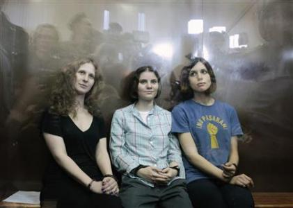 "Members of the female punk band ""Pussy Riot"" (R-L) Nadezhda Tolokonnikova, Yekaterina Samutsevich and Maria Alyokhina sit in a glass-walled cage after a court hearing in Moscow, August 17, 2012. REUTERS/Maxim Shemetov"