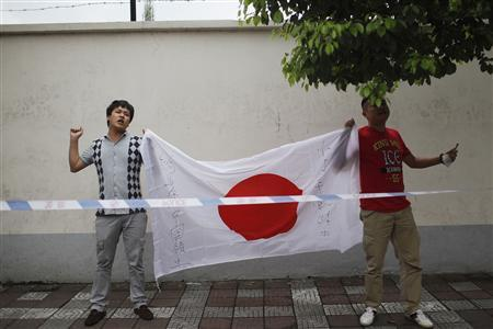 Demonstrators wave a Japanese national flag during an anti-Japan protest outside the Japanese consulate in Shanghai September 14, 2012. REUTER/Aly Song