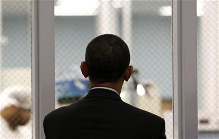U.S. President Barack Obama watches workers through a window as he tours Celgard Inc. in Charlotte, North Carolina April 2, 2010. REUTERS/Kevin Lamarque