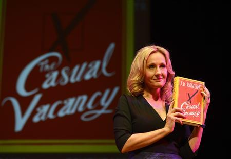 "Author J.K Rowling poses for photographers with a copy of her adult fiction book ""The Casual Vacancy"", at the Queen Elizabeth Hall in London September 27, 2012. REUTERS/Paul Hackett"