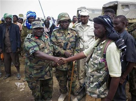 A senior commanding officer (front L) of the African Union Mission in Somalia (AMISOM) shakes hands with a defected commander (front R) of Islamist militant group al Shabaab after members gave themselves up to AMISOM forces in Garsale, approximately 10km from the town of Jowhar, 80km north of Mogadishu, in this September 22, 2012 handout picture made available by the African Union-United Nations Information Support Team on September 23, 2012. REUTERS/AU-UN IST/Abukar Albadri/Handout
