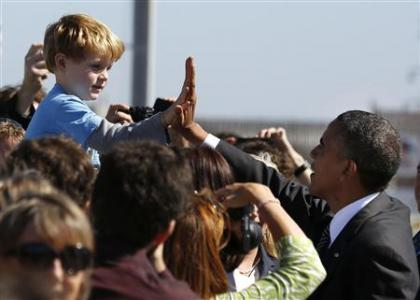 U.S. President Barack Obama high-fives with Max Frank, 4 years old, from Livermore after Obama arrives at San Francisco International Airport to continue a three day campaign swing in California and Ohio, October 8, 2012. REUTERS/Larry Downing
