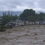 Heavy rains from Hurricane Sandy causes the Croix de Mission river to swell to levels that threaten to flood the homes along its bank in Port-au-Prince October 25, 2012. REUTERS/Swoan Parker
