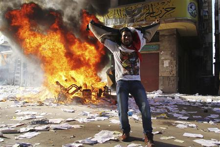 A protester cheers as items ransacked from an office of the Muslim Brotherhood's Freedom and Justice Party burn in Alexandria November 23, 2012. REUTERS/Stringer