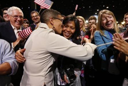 Keesha Patterson of Ft. Washington, Maryland (L) kisses her girlfriend Rowan Ha (R) after proposing marriage, during the election night victory rally at re-elected President Barack Obama headquarters in Chicago, November 6, 2012. REUTERS/Kevin Lamarque/Files
