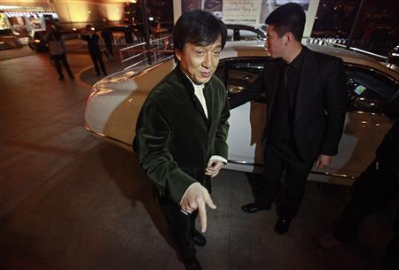 """Kung Fu superstar Jackie Chan gestures in front of a car before having his Bentley 666 auctioned for charity in Beijing, November 19, 2012. Chan said that while the upcoming film """"Chinese Zodiac 2012"""" will be his last major action movie, citing his increasing age, he will still be packing punches in the world of philanthropy. Chan wrote, directed and produced his latest film, set to premiere in cinemas next month. He also plays the lead role and said that it was probably his """"best film for myself"""" in the last ten years. Picture taken November 19, 2012. REUTERS/Petar Kujundzic"""