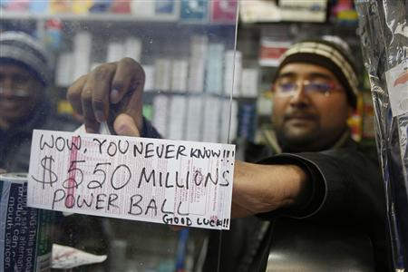 A worker pastes an updated Powerball sign up in New York, November 28, 2012. Dreams of vast riches from a record Powerball jackpot of at least half-a-billion dollars drove enthusiastic ticket-buying across the United States ahead of the Wednesday night draw, and continued heavy sales could nudge the payout higher, authorities said. REUTERS/Carlo Allegri