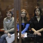 """Members of the female punk band """"Pussy Riot"""" (L-R) Yekaterina Samutsevich, Maria Alyokhina and Nadezhda Tolokonnikova sit in a glass-walled cage before a court hearing in Moscow October 10, 2012. REUTERS/Maxim Shemetov"""