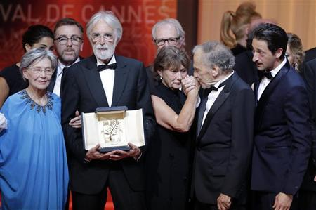 "Director Michael Haneke (2ndL), actress Emmanuelle Riva (L) and actor Jean-Louis Trintignant (2ndR) react after receiving the Palme d'Or award for the film ""Amour"" (Love) during the awards ceremony of the 65th Cannes Film Festival, May 27, 2012. REUTERS/Eric Gaillard"