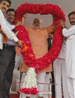 Gujarat's Chief Minister Narendra Modi (C) receives a rose garland by his supporters during an election campaign rally ahead of the state assembly elections at Fagvel village in the western Indian state of Gujarat October 11, 2012. REUTERS/Amit Dave
