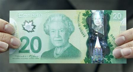 The new Canadian 20 dollar bill made of polymer is displayed at the Bank of Canada in Ottawa in this May 2, 2012, file photo. Canada is known for the sugar maple, emblazoned on its red-and-white flag, but the Bank of Canada has put what one careful botanist says is a foreign Norway maple leaf on its new currency. The untrained eye might not at first spot the difference between the maple leaf on the new $20, $50 and $100 bills and the sugar maple that is endemic to North America. REUTERS/Chris Wattie/Files