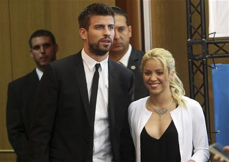 Colombian pop star and the United Nations Children's Fund (UNICEF) ambassador, Shakira, walks with her boyfriend, Barcelona soccer player Gerard Pique, after her joint news conference with Israel's president Shimon Peres (not seen) at the 3rd annual Israeli Presidential Conference in Jerusalem June 21, 2011. REUTERS/Ronen Zvulun
