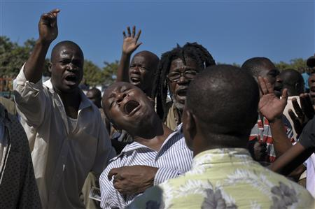 Supporters of former Haitian President Jean-Bertrand Aristide react outside a courthouse in Port-au-Prince January 3, 2013. Aristide on Thursday won a delay until next week in a court hearing to address accusations he exploited former street children for political gain. REUTERS/Swoan Parker
