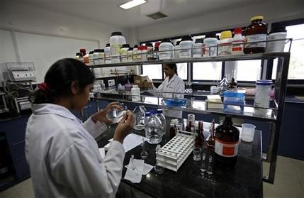 FILE - In this March 13, 2012 file photo, Indian scientists work inside a laboratory of the Research and Development Centre of Natco Pharma Ltd. in Hyderabad, India.  From Africa's crowded AIDS clinics to the malarial jungles of Southeast Asia, the fate of millions of people awaits a ruling by India's highest court that could determine whether the country's drug companies can continue to provide cheap versions of many life-saving medicines. (AP Photo/Mahesh Kumar A., File)
