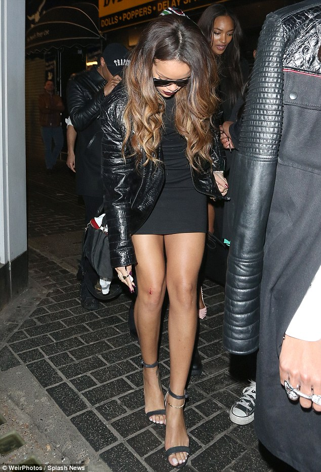 Ouch! Rihanna touches her leg where it was grazed, as if it had only just happened