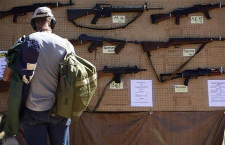 A man look at different rental guns displayed during the Big Sandy Shoot in Mohave County, Arizona March 22, 2013. REUTERS/Joshua Lott