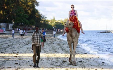 A tourist rides on a camel's back at the Jomo Kenyatta public beach in Kenya's coastal city of Mombasa, March 24, 2013. Kenya's tourism industry may be a swift winner from the election of Uhuru Kenyatta, owner of hotels and a vast business empire, as east Africa's biggest economy seeks to benefit from a vote that avoided a re-run of bloodshed of five years ago. Picture taken March 24, 2013. To match story KENYA-ECONOMY/TOURISM REUTERS/Joseph Okanga (KENYA - Tags: TRAVEL POLITICS BUSINESS ANIMALS)