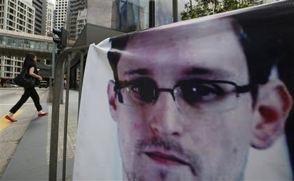 A banner supporting Edward Snowden, a former CIA employee who leaked top-secret documents about sweeping U.S. surveillance programs, is displayed at Central, Hong Kong's business district, Thursday, June 20, 2013. A WikiLeaks spokesman who claims to represent Snowden has reached out to government officials in Iceland about the potential of the NSA leaker applying for asylum in the Nordic country, officials there said Wednesday.  (AP Photo/Kin Cheung)