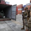 """Panama police officers stand guard in front of a container holding a green missile-shaped object seized from the North Korean flagged ship """"Chong Chon Gang"""" at the Manzanillo Container Terminal in Colon City July 17, 2013. REUTERS/Carlos Jasso"""