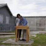 U.S. President Barack Obama, right, and first lady Michelle Obama write in a guest book after touring Robben Island, the historic Apartheid-era prison that held former South African president and anti-apartheid hero Nelson Mandela, Sunday, June 30, 2013, in Robben Island, South Africa. (AP Photo/Evan Vucci)