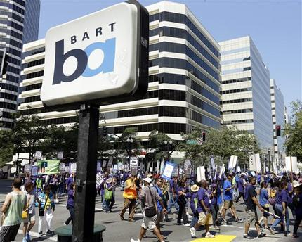 In this file photo from Monday, July 1, 2013, striking Bay Area Rapid Transit workers picket as they close the intersection of 14th & Broadway on Monday, July 1, 2013, in downtown Oakland, Calif. San Francisco Bay Area commuters braced for the possibility of another train strike as the Bay Area Rapid Transit agency and its workers approached a deadline to reach a new contract deal. The two sides were set to resume negotiations at noon on Thursday, Aug. 1, but did not appear close to an agreement. (AP Photo/Ben Margot)