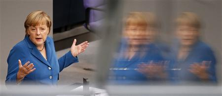 German Chancellor Merkel is reflected in a window as she gives a speech during a debate of the lower house of parliament Bundestag in Berlin
