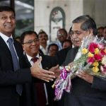 Newly appointed governor of RBI Rajan receives a bouquet from RBI deputy governor Chakrabarty in Mumbai