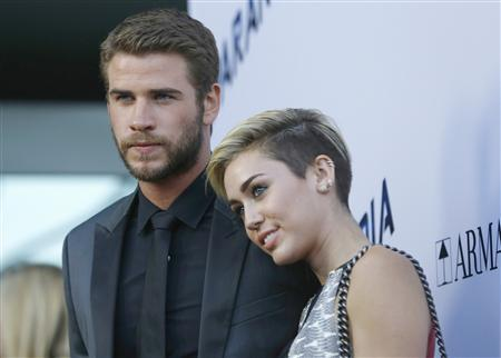 """Hemsworth poses with Cyrus at premiere of """"Paranoia"""" in Los Angeles"""