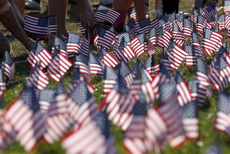 People plant some of the 3000 U.S. flags placed in memory of the lives lost in the September 11, 2001 attacks, at a park in Winnetka