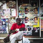 African migrant sits on a street corner in south Tel Aviv